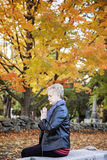 Woman praying in cemetery. A side view of an elderly woman sitting on a bench praying in a cemetery royalty free stock photography