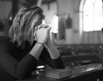 Woman praying in the church grayscale Royalty Free Stock Photo