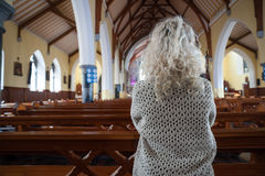 Woman praying in church Stock Photos