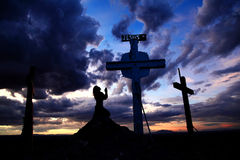 Woman Praying at Cross in Sunset Stock Image