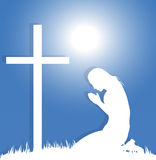 Woman praying before the crucifix. Silhouette of woman praying before the crucifix Stock Image