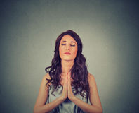 Woman praying eyes closed on gray wall background. Closeup portrait of a young woman praying eyes closed on gray wall background Stock Photos