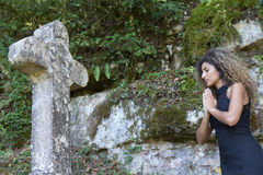 Woman praying in front of a stone Stock Images