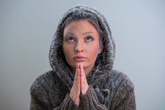 Woman praying with frost on her face Stock Image