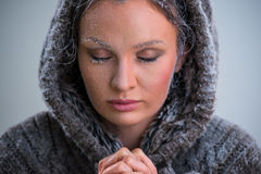 Woman praying with frost on her face Stock Images