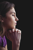 Woman praying with hands together. On black background Royalty Free Stock Photos