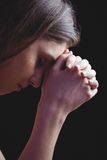 Woman praying with hands together. On black background Stock Photography