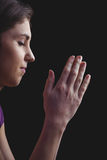 Woman praying with hands together. On black background Royalty Free Stock Photo
