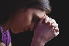 Woman praying with hands together. On black background Royalty Free Stock Image