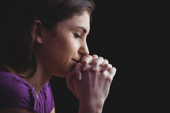 Woman praying with hands together. On black background Royalty Free Stock Images