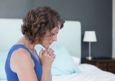 Woman praying hopeful and sad next to bed. Digital composite of Woman praying hopeful and sad next to bed Royalty Free Stock Photography