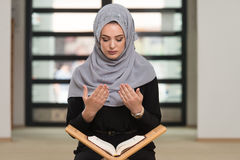 Woman Praying In The Mosque And Reading Quran. Muslim Woman Reading Koran Or Quran Wearing Traditional Dress At The Mosque Royalty Free Stock Images