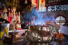 Woman praying  for new year ,Lighting incense to Buddha. Burning joss stick and oil palm candle at chinese shrine for making merit in chinese new year festival Royalty Free Stock Photos