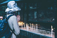 Woman praying next to candles Royalty Free Stock Images