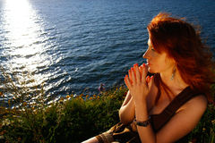 Woman praying by ocean Stock Images