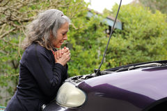 Woman praying over her car Stock Photography