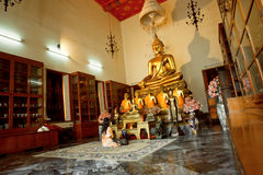 Woman praying past Buddha statue inside small temple room of historical monastery Stock Photos