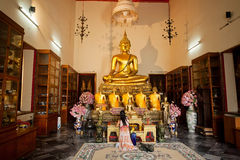 Woman praying past Buddha statue inside small temple room of historical monastery Stock Photography