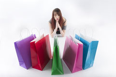 Woman in Praying Pose In Front of Shopping Bags Royalty Free Stock Image