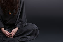 Woman praying. Prayer dressed in Vestments of a nun on gray studio background. Religion and hope concept.  Stock Image