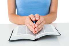 Woman praying while reading bible Stock Images
