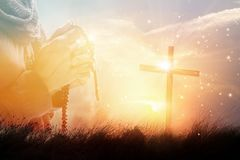 Woman praying with rosary beards and cross on nature sunset. Double exposure. Woman praying with rosary beards and symbolic cross on nature sunset background stock photos