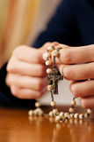 Woman praying with rosary to God. Woman (only closeup of hands to be seen) with rosary sending a prayer to God, the dark setting suggests she is sad or lonely Royalty Free Stock Photography