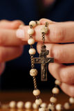 Woman praying with rosary to God. Woman (only closeup of hands to be seen) with rosary sending a prayer to God, the dark setting suggests she is sad or lonely Royalty Free Stock Image