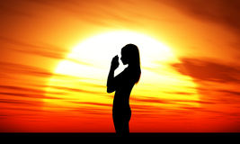 Woman praying at sunset Stock Image