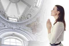 Woman praying in a temple. Profile of young beautiful brunette woman praying in a bright barocco church Royalty Free Stock Photography