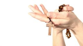 Woman holding a rosary beads cross in her hands stock image