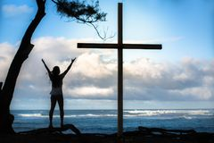 Woman celebrates next to a large crucifix facing the ocean. A woman praying to God next to a cross, with hands in the air Stock Photography