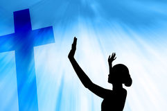 Woman praying under the cross Royalty Free Stock Photo