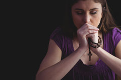 Woman praying with wooden rosary beads. On black background stock image