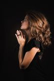 Woman prays on a  black background Royalty Free Stock Photos