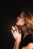 Woman prays on a  black background Stock Image