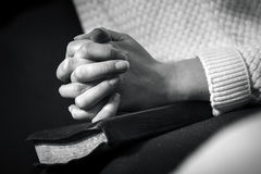 Woman prays with folded hands on the bible Royalty Free Stock Photo