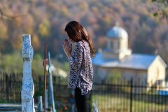 woman prays in front of a cross in the cemeter Stock Image