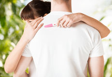 Woman with pregnancy test hugging man. Family, parenting and medical concept - women with pregnancy test hugging man royalty free stock photo