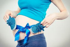 Woman in pregnant with blue ribbon and baby shoes on belly, concept of expecting for boy. Woman in pregnant with blue ribbon and baby shoes on her belly, concept stock images