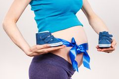 Woman in pregnant with blue ribbon on belly and baby shoes, concept of expecting for boy royalty free stock images