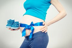 Woman in pregnant with blue ribbon on belly holding baby shoes, concept of expecting for boy royalty free stock photo