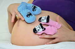 Woman pregnant with little socks stock photos