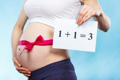 Woman in pregnant with pink ribbon on belly and inscription 1+1=3, concept of extending family stock photo