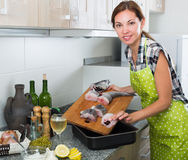 Woman preparating fresh fish steaks. Happy woman preparating fresh fish steaks of haddock with peas and wine-lemon dressing Royalty Free Stock Images