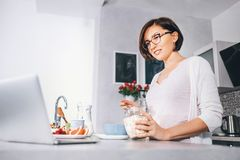 Woman prepare breakfast and watch a news in laptop Stock Image