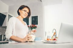 Woman prepare breakfast and watch a news in laptop Royalty Free Stock Photo