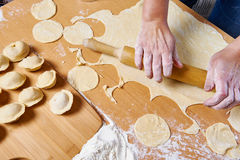 Woman prepare dough with rolling pin for dumplings Stock Photos