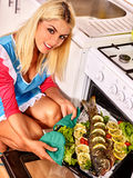 Woman prepare fish in oven Royalty Free Stock Photo