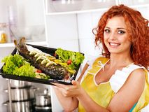 Woman prepare fish in oven. Happy woman prepare fish at oven-tray Royalty Free Stock Photography